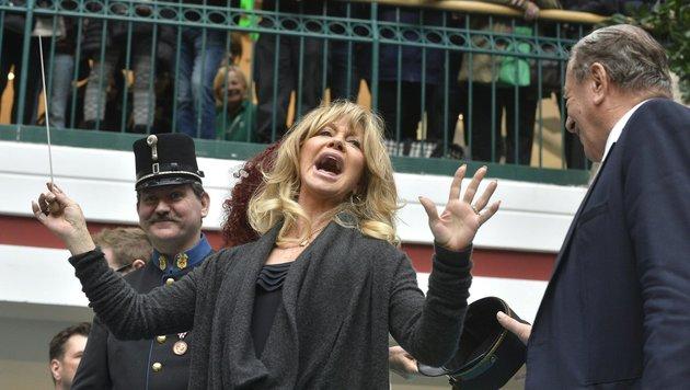 Goldie Hawn dirigiert eine Blasmusikkapelle im Rahmen der Autogrammstunde in der Lugner City. (Bild: APA/HERBERT PFARRHOFER)