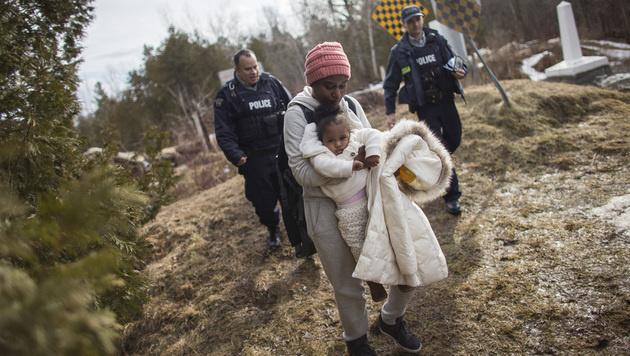 Kanadische Grenzpolizisten mit einer aus den USA geflohenen sudanesischen Frau (Bild: AFP)