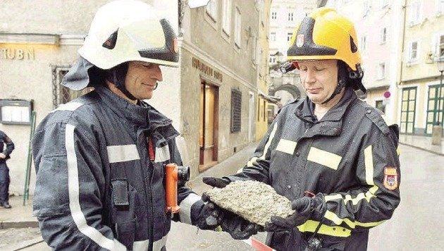 Feuerwehrmänner mit einem der Steine aus der Mönchsbergwand, die in der Gstättengasse landeten. (Bild: Info-Z/Killer)