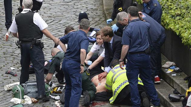 Der britische Staatssekretär Tobias Elwood (Mitte, im Anzug) war einer der ersten Helfer vor Ort. (Bild: AP)