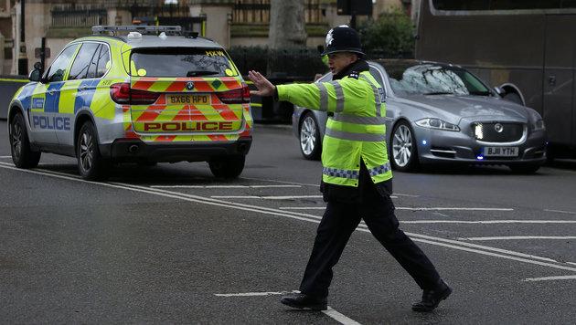 Ein Polizist hält herankommende Fahrzeuge auf. (Bild: AFP)