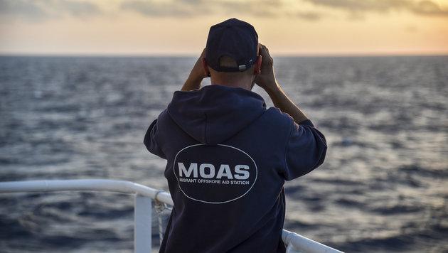 Ein Mitglied der NGO MOAS hält  Ausschau nach Bootsflüchtlingen. (Bild: AFP)