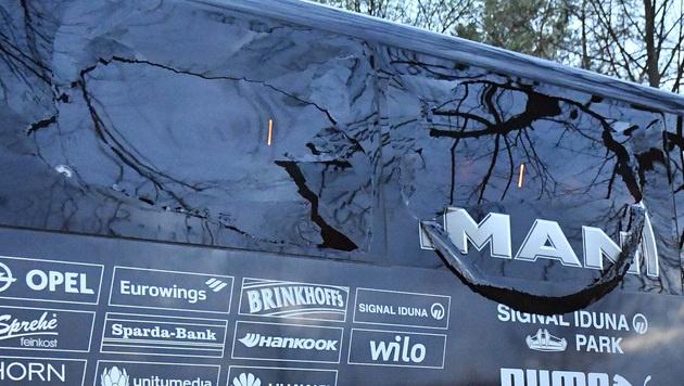 Die Scheibe des Teambusses wurde zerstört. (Bild: AP)