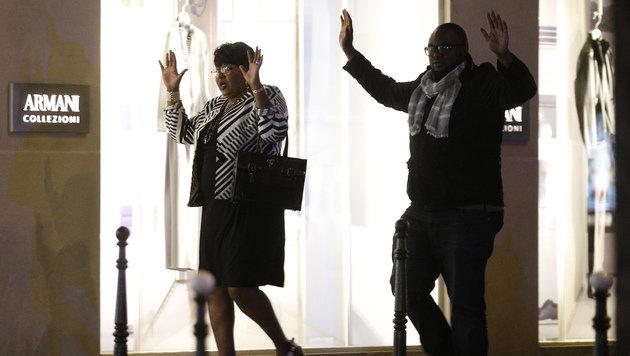 Spaziergänger passieren die Polizeisperren mit erhobenen Händen. (Bild: AP)