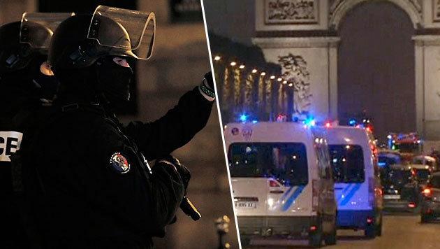 Schwer bewaffnete Polizisten, die abgeriegelten Champs-Elysees und Blaulicht, wohin das Auge reicht (Bild: AFP)