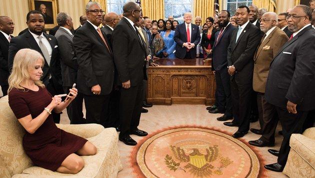 Kellyanne Conway hockt beim Gruppenfoto Trumps mit Uni-Professoren in Bambi-Pose am Sofa. (Bild: AFP)