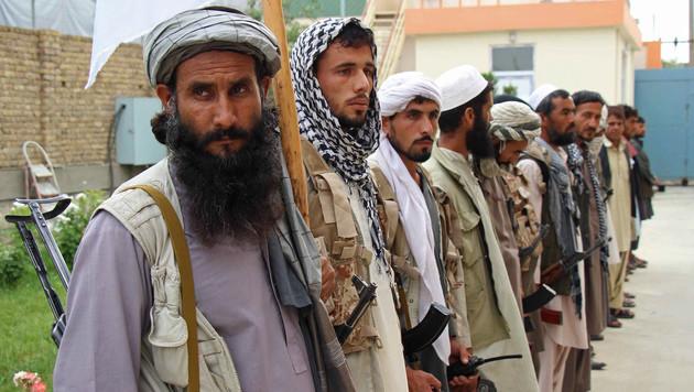 Taliban-Kämpfer, die ihre Waffen freiwillig abgeben (Bild: AFP)