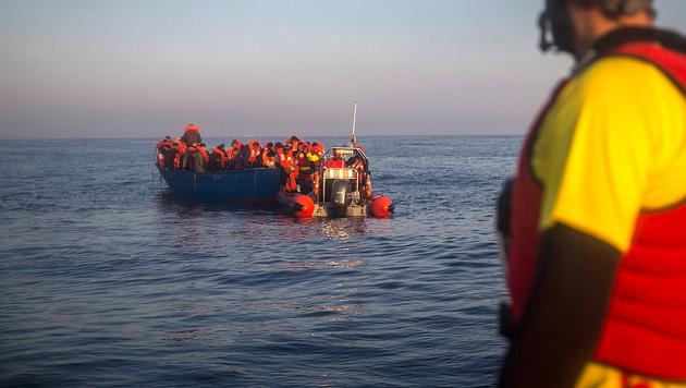 Die spanische NGO Proactiva Open Arms bei der Versorgung eines Flüchtlinsgbootes (Bild: AP)