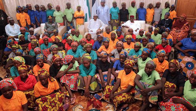 Präsident Buhari inmitten der 82 freigelassenen Chibok-Mädchen (Bild: AP)