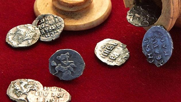 Acht der zehn in der Schachfigur (am oberen Bildrand) gefundenen Münzen (Bild: Stadtverwaltung Moskau)