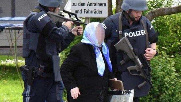 Eine betagte Dame wird von Polizisten in Sicherheit gebracht. (Bild: APA/ZOOM.TIROL)