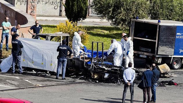 Tatortermittler inspizieren die Überreste des total ausgebrannten Wohnmobils. (Bild: AP/ANSA/Massimo Percossi)