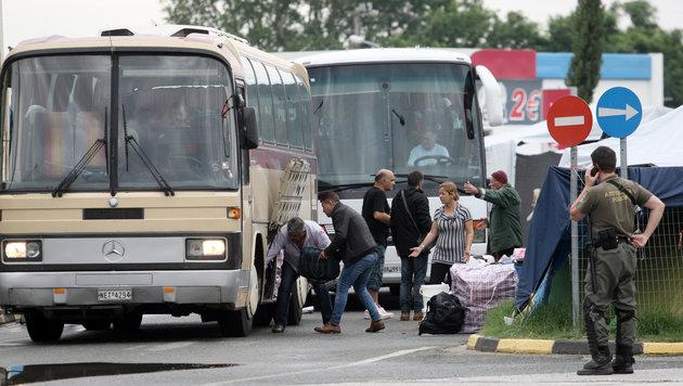 Flüchtlinge laden ihr Gepäck in Busse, bevor es aus Griechenland nach Westeuropa geht. (Bild: AFP)