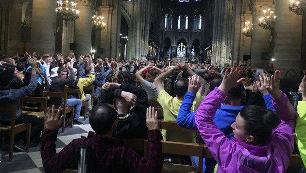 Notre-Dame-Besucher mit erhobenen Händen unmittelbar nach dem Angriff auf Polizisten vor der Kirche. (Bild: AP)