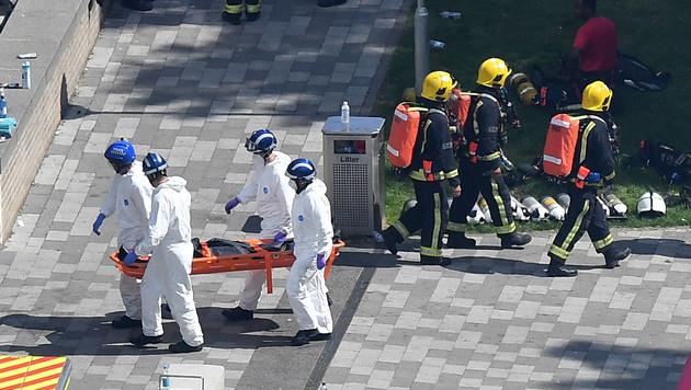 Helfer transportieren eine Leiche vom Gelände ab. (Bild: AFP)