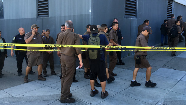 Angestellte der UPS-Zentrale werden von der Polizei in Sicherheit gebracht. (Bild: AP)