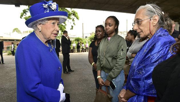 Königin Elizabeth II. spricht mit obdachlos gewordenen Menschen in einer Notunterkunft in London. (Bild: AP)