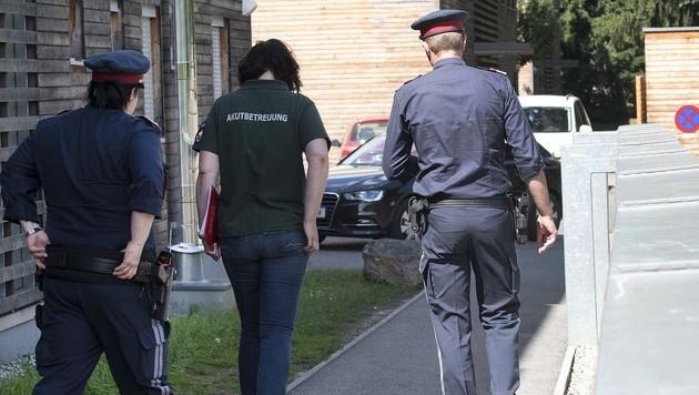 Eine Mitarbeiterin der Akutbetreuung mit Polizisten am Tatort. (Bild: APA/ELMAR GUBISCH)