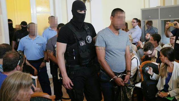 Maskierte Beamte führten die Angeklagten in den Gerichtssaal. (Bild: APA/GEORG HOCHMUTH)