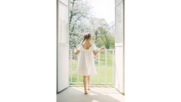 Barfuß im weißen Sommerkleid steht Prinzessin Estelle am Balkon und schaut in den Garten. (Bild: Photo: Erika Gerdemark Kungahuset.se)