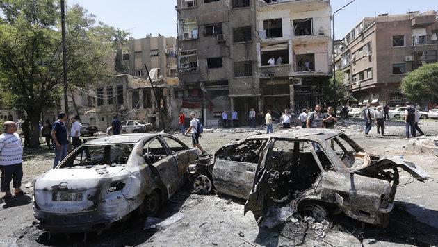 Völlig ausgebrannte Autowracks am Explosionsort (Bild: AFP)
