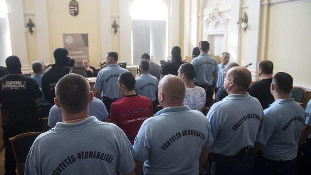 Die zehn Angeklagten umringt von Justizwachebeamten im großen Gerichtssaal von Kecskemet (Bild: AP)