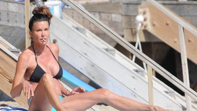 Model Janice Dickinson mit Zigarette am Strand. (Bild: www.PPS.at)