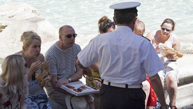 Touristen werden von einem Polizisten aufgefordert, nicht am Trevi-Brunnen Pizza zu essen. (Bild: EPA)