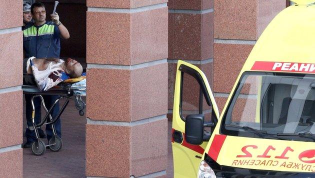 Ein Verletzter wird nach dem Vorfall im Moskauer Gericht abtransportiert. (Bild: AP)