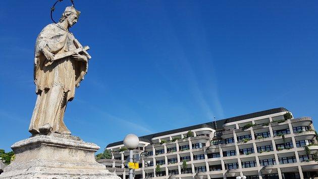 Einen skeptischen Blick wirft der Brückenheilige auf das Neue Linzer Rathaus in Urfahr. (Bild: Werner Pöchinger)