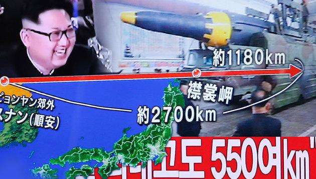 Nordkoreas Machthaber Kim Jong Un freut sich über die Reichweite der jüngst abgeschossenen Rakete. (Bild: AP,krone.at-Grafik)