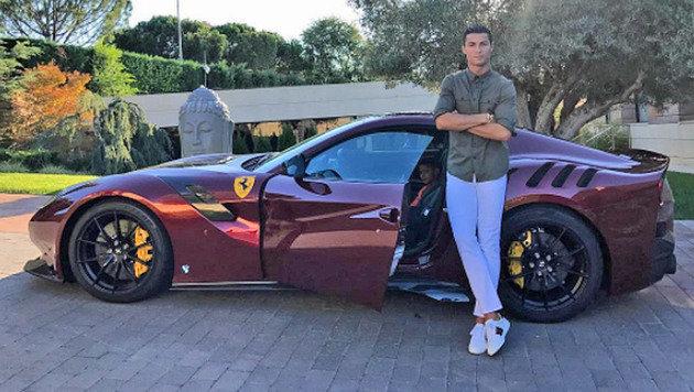 Er zeigt schon immer gerne, was er hat: Cristiano Ronaldo posiert vor seinem Ferrari. (Bild: Instagram)