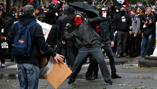 Vermummte Demonstranten werfen Steine gegen die Sicherheitskräfte. (Bild: AP)