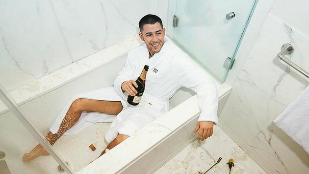 Nick Jonas macht es sich mit Champagner und Bademantel in der Wanne gemütlich. (Bild: www.PPS.at)