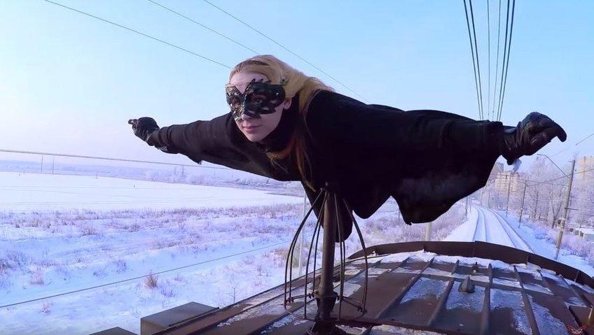 Batgirl (19) surft auf Zugdach durch Russland  (Bild: Kobzarro)