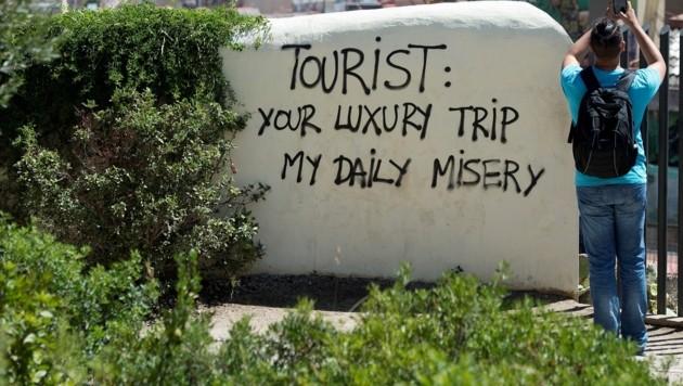 """""""Dein Luxustrip ist mein tägliches Elend"""" - Schriftzug auf einer Wand in Barcelona (Bild: AFP)"""