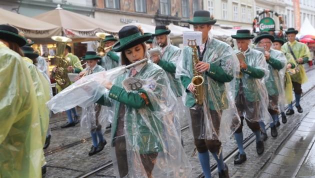 Gut behütet - und mit Regenschutz - marschierten die Musiker in der Grazer City auf. (Bild: Jürgen Radspieler)