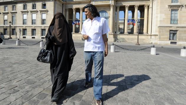 Rachid Nekkaz mit einer Burkaträgerin (Bild: AFP)