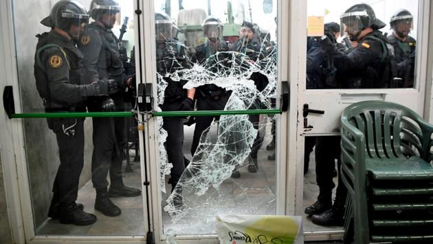 Polizeieinheiten brechen die Tür zu einem Wahllokal auf. (Bild: APA/AFP/LLUIS GENE)
