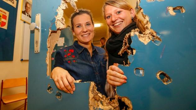 Die Lehrerinnen Julia und Anna zeigen das Loch, das die Täter in die Konferenzzimmer-Tür schlugen. (Bild: MARKUS TSCHEPP)