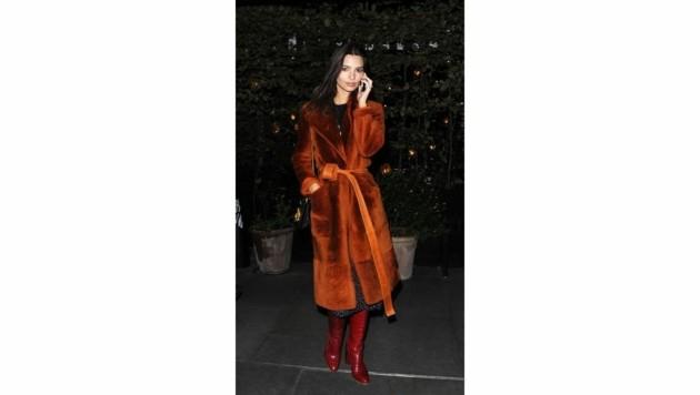 Emily Ratajkowski kombiniert ihren rostbraunen Mantel mit roten Stiefeln und zarten Stoffen. (Bild: www.PPS.at)