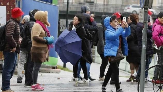 Der Kampf mit dem Schirm: Viele Touristen hatten es am Sonntag schwer. (Bild: Markus Tschepp)