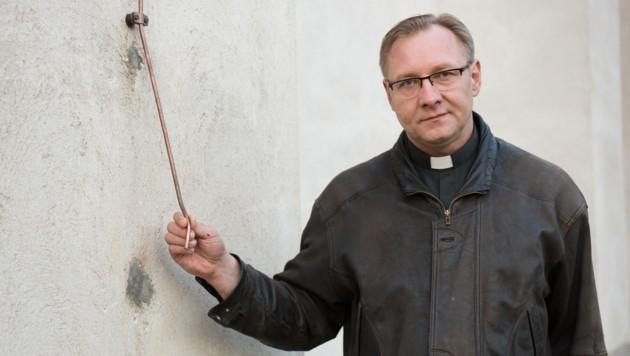 Der traurige Herr Pfarrer: Mariusz Ratynski mit den Resten des Blitzableiters (Bild: IMRE ANTAL)