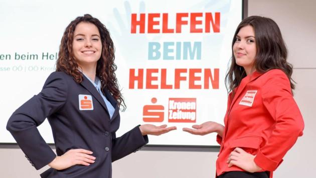 Lisa (Sparkasse OÖ) und Rrezarta (Krone) mit dem Helfen beim Helfen Logo. (Bild: Markus Wenzel)