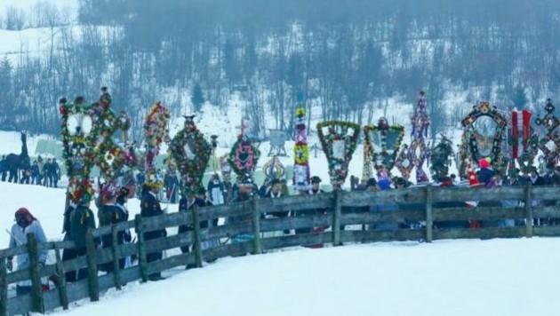 Der Perchtenzug kommt um 7.30 Uhr über schneebedeckte Hügel in den Hofgasteiner Ortsteil Gadaunern. (Bild: Gerhard Schiel)