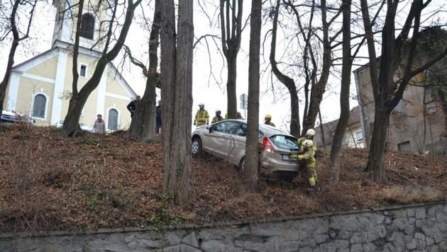 Das Auto rollte rückwärts von der Kirche über die Böschung. Blieb zum Glück an einem Baum hängen.