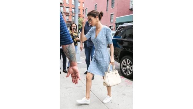 Selena Gomez trägt eine nudefarbige Tasche zum blauen Sommerkleidchen.