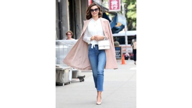 Miranda Kerr weiß, wie's geht: Zu Jeans und weißer Bluse kombiniert sie einen rosa Mantel und eine weiße Mini-Bag.