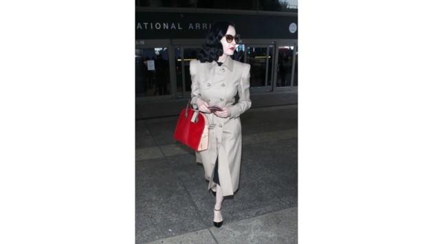 Eine echte Lady: Dita Von Teese im Trenchcoat mit roter Louis-Vuitton-Tasche