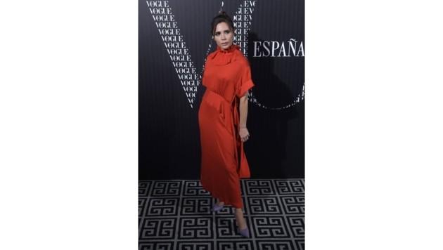 Victoria Beckham im roten Kleid. Sie kombiniert fliederfarbene Pumps dazu.